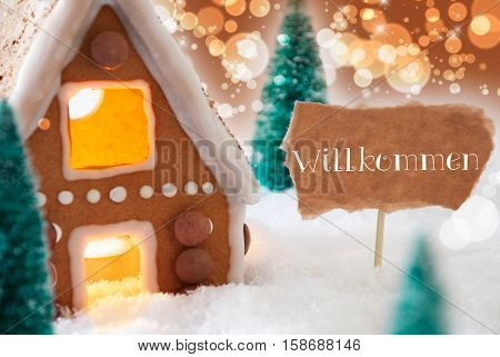 Gingerbread House In Snowy Scenery As Christmas Decoration. Christmas Trees And Candlelight. Bronze And Orange Background With Bokeh Effect. German Text Willkommen Means Welcome