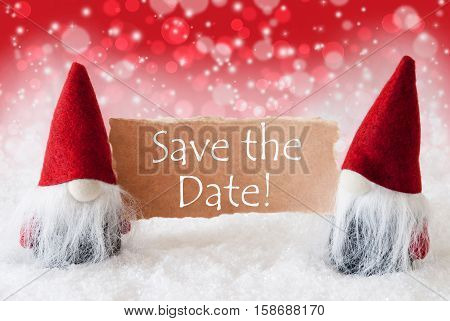 English Text Save The Date. Christmas Greeting Card With Two Red Gnomes. Sparkling Bokeh And Christmassy Background With Snow.
