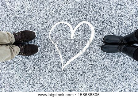 Men and women's boots standing at abstract heart symbol on asphalt covered gritty snow surface. Rough snowy. Cold Winter. Top view. Relations concept