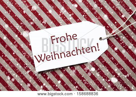 One Label On A Red And Brown Striped Wrapping Paper. Textured Background With Snowflakes. Tag With Ribbon. German Text Frohe Weihnachten Means Merry Christmas,