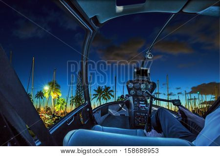 Helicopter cockpit flies in Ala Wai Harbor, Honolulu by night, Oahu, Hawaii, with pilot arm and control board inside the cabin.