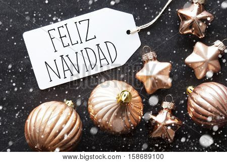 Label With Spanish Text Feliz Navidad Means Merry Christmas. Bronze Christmas Tree Balls On Black Paper Background With Snowflakes. Christmas Decoration Or Texture. Flat Lay View