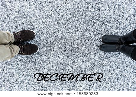 Male and Female boots standing at heart symbol with text december on asphalt covered gritty snow surface. Rough snowy. Winter love. Top view. Relations concept