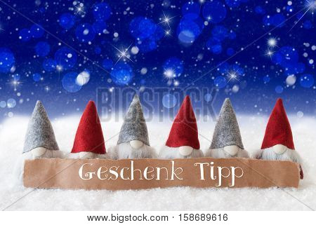 Label With German Text Geschenk Tipp Means Gift Tip. Christmas Greeting Card With Gnomes. Sparkling Bokeh And Blue Background With Snow, Snowflakes And Stars.