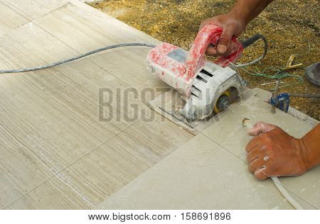 Man using electric tile cutter using water ripped the tiles to get the tiles for flooring and ceramic.