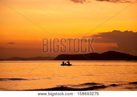Silhouette of people rowing boat on the sea at sunset