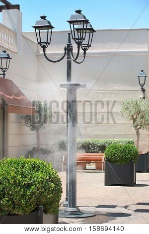 Sprinklers splashing vaporized water at street in order to cool the hot summer temperature in Italy