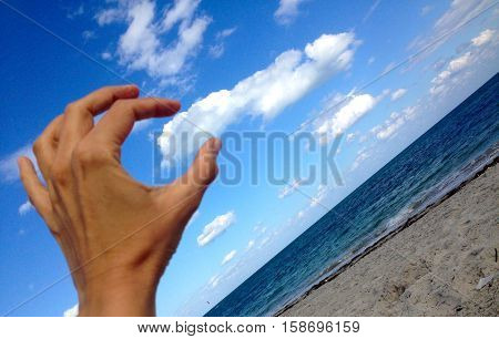 hand grabbing cloud at the sunny beach