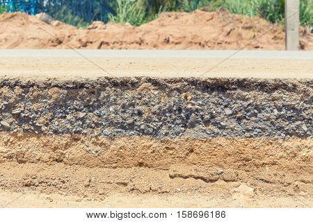 Cross section of asphalt road with blue sky background.