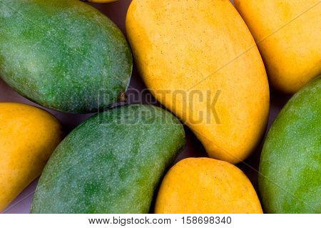 a pile yellow ripe mango and fresh green mango  on white background healthy fruit food isolated