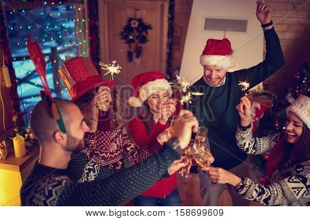 Cheerful friends toasting at New Year's midnight