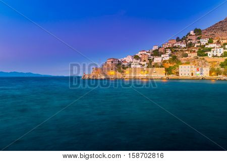 Hydra island in a summer evening in Greece. Beautiful landscape with sea and island at sunset lit with purple light.
