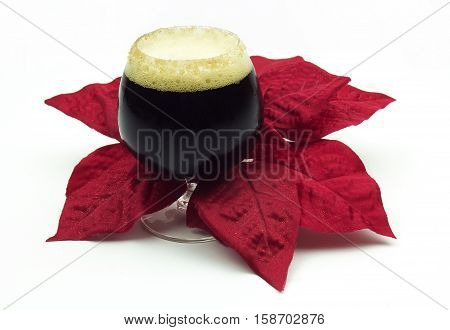 Christmas Ale sitting among a holiday poinsettia