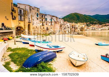 Boats on the beach of habour and old houses in Cefalu at sunset, Sicily. Beautiful townscape of old italian town. Travel photography.
