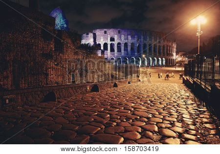Colorful Colosseum at night with stone pattern street, the world known landmark and the symbol of Rome, Italy.