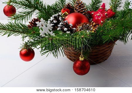 Christmas red ornaments and snowy decorated pine cone table centerpiece. Christmas background with arrangement in wicker basket.