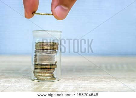 Man's hand putting a money coin in a stack in a glass jar. Saving money. Growing business. Light background.