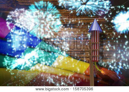 3D Rocket for fireworks against colourful fireworks exploding on black background