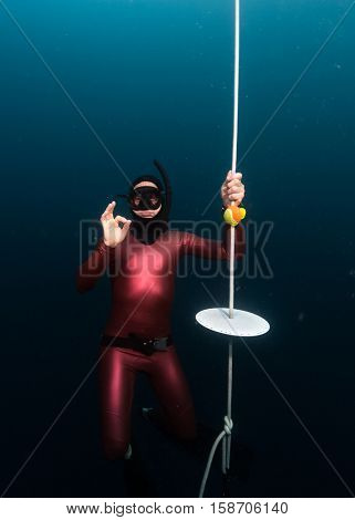 Free divers showing OK sign hanging on a depth by the end of training line