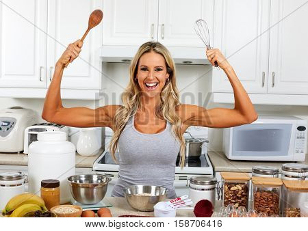 Happy woman with whisk and wooden spoon.