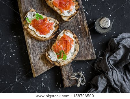 Smoked salmon and cream cheese sandwich. On a rustic wooden cutting board on a dark background top view. Delicious appetizers with wine snack or breakfast