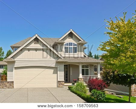 Average family house with concrete driveway to the garage on blue sky background