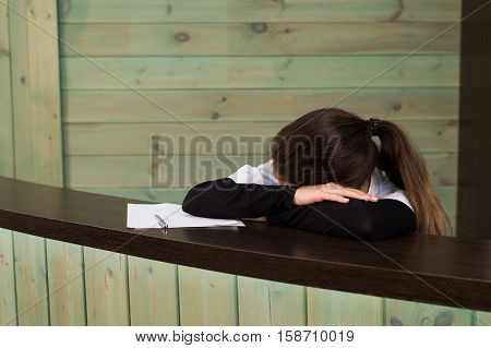 The female doctor sits at a table having closed eyes for fatigue.