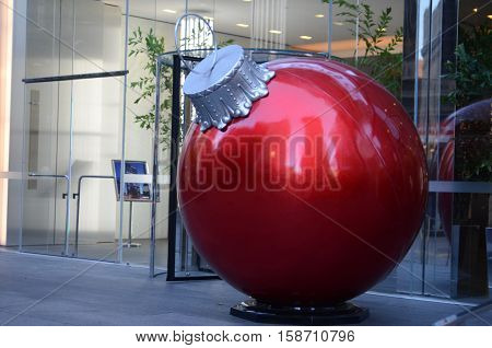 Large Christmas bauble decoration in front of generic office block