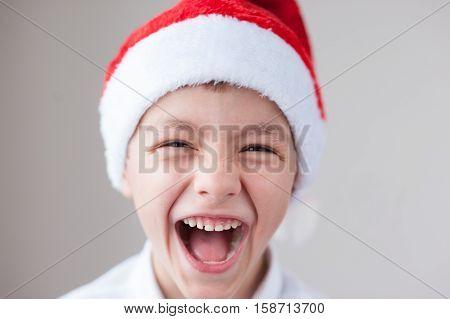 cute little boy in Santa hat laughs showing teeth