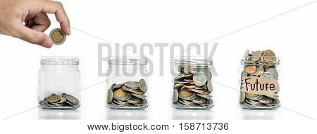 Money saving, Hand putting coin in glass jar with coins inside growing up, on white background, concept of saving money for future