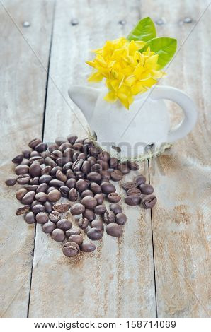 Coffee Beans On Grunge Wood Background With Ixora Flower Pot