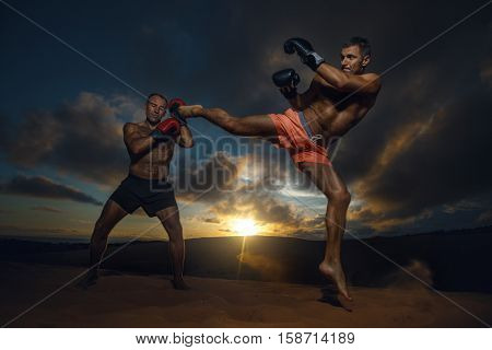Strong boxer doing  kickboxing exercise with trainer at sunset.