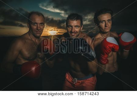 Intense tough buff strong partners weight training friends serious expression fighters  at sunset