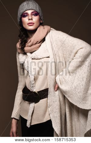 Beautiful sexy long-haired brunette woman in knitted clothes posing in the studio. The beauty of the face and body. Photos shot in a studio
