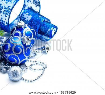 Christmas and New Year Blue color Decoration isolated on white background. Border art design with holiday baubles. Beautiful Christmas tree closeup decorated with Ball, tinsel and ribbon. Copyspace