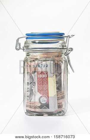 Old thousand Indian rupees currency notes sealed in a glass jar.