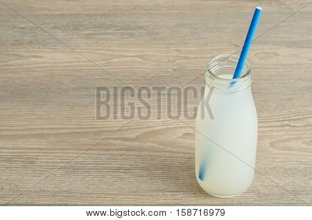 Litchi juice in a glass bottle with a blue straw