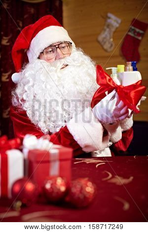 Santa preparing Christmas presents for women beuty products