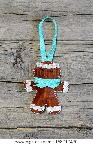 Christmas gingerbread man isolated on old wooden background. Funny felt gingerbread man ornament. Christmas symbol. Top view. Closeup