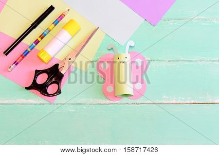 Pretty paper butterfly crafts, scissors, marker, glue stick, colored paper, pencil on green wooden table. Tools and materials to create kids crafts. Summer preschooler handicraft idea. Top view