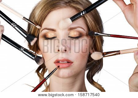 Many hands with cosmetics brushes doing make-up to glamour woman, isolated on white