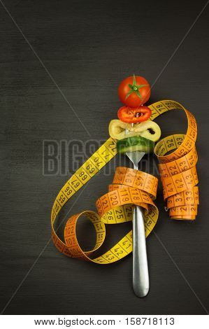 Mixed vegetables on a fork. Diet concept. The risk of obesity. Fresh food diet. Raw vegetables on a black table.