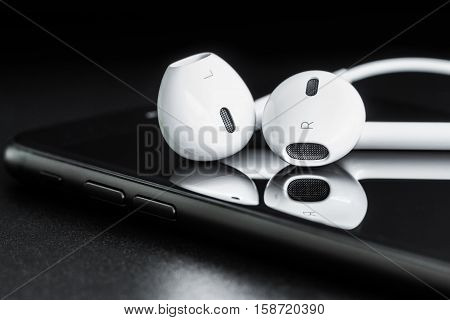 Close-up headphone stack on phone modern phone's earbuds device accessories
