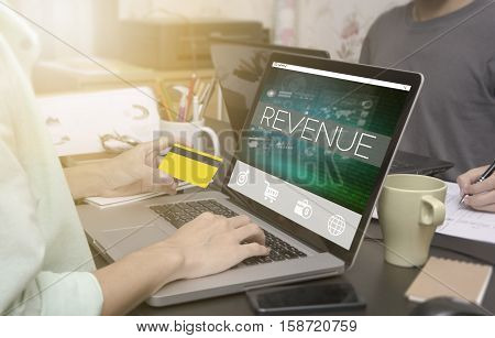 business hand typing on computer keyboard with credit card and Revenue homepage on the computer screen business freelance concept.
