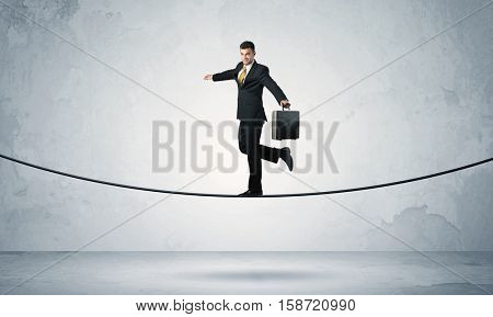 A confident businessman with briefcase walking ahead on a tightrope in empty grey urban space concept