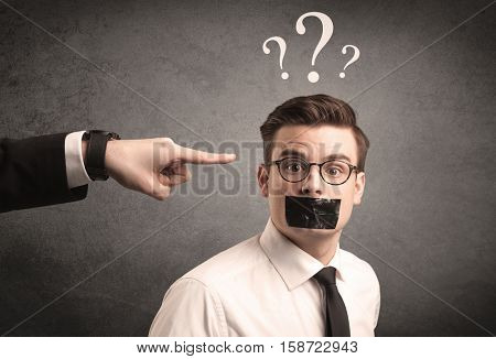 Caucasian business hand pointing at scared employee with big white question marks above his head