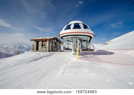 Ski lift station in mountains at winter. Alpine winter mountain landscape. French Alps covered with snow in sunny day. Val-d'Isere, Alps, France