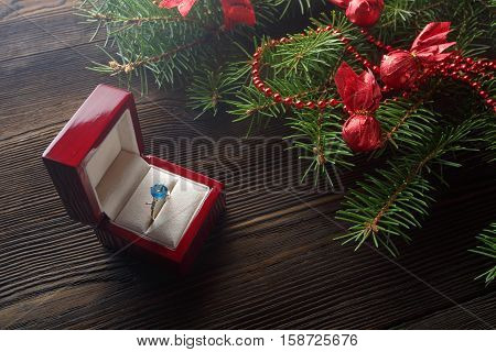 Christmas wooden background with Christmas tree and red ornaments. Christmas background with red wooden box. A Christmas gift. Gift on Valentine's Day. Jewelry red wooden box. Ring with blue gem