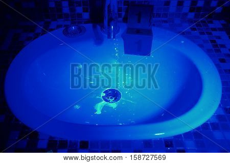 Wash basin with stains under UV light