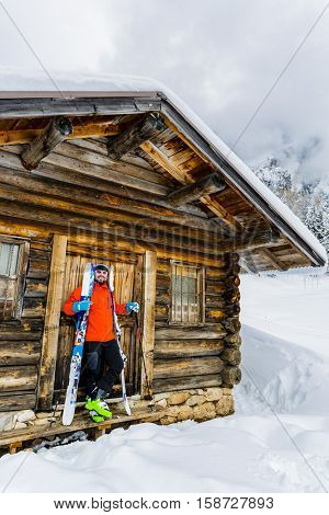 Skier standing in front of mountain hut. Ski touring in wonderful winter scenery with snow and timber cabin chalet home.